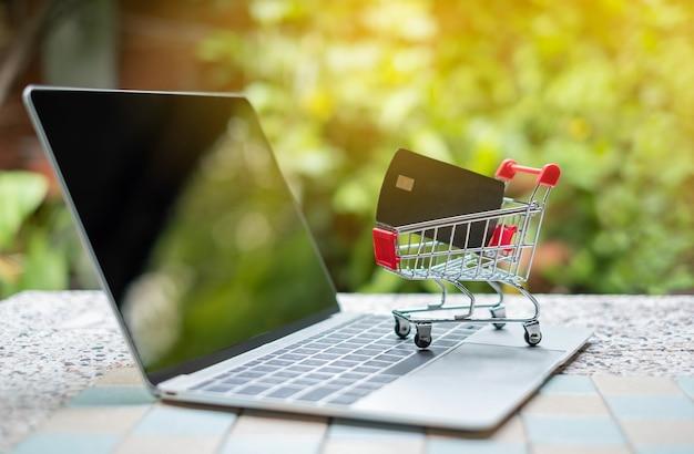 Tarjeta de crédito en el pequeño carro de compras en la computadora portátil. conceptos de compras en línea