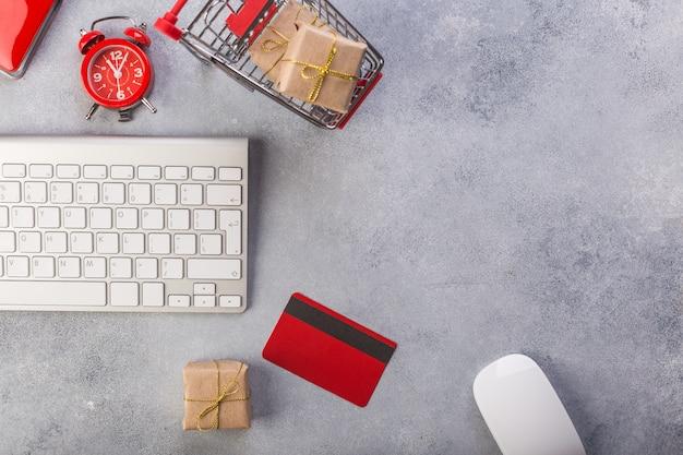 Tarjeta de crédito roja, teclado y regalos de navidad en mesa gris plana, copia espacio.