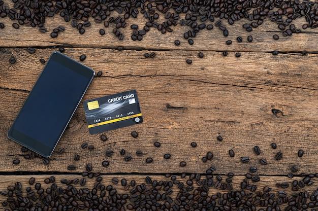 Tarjeta de crédito de smartphone y granos de café en la vista superior del escritorio