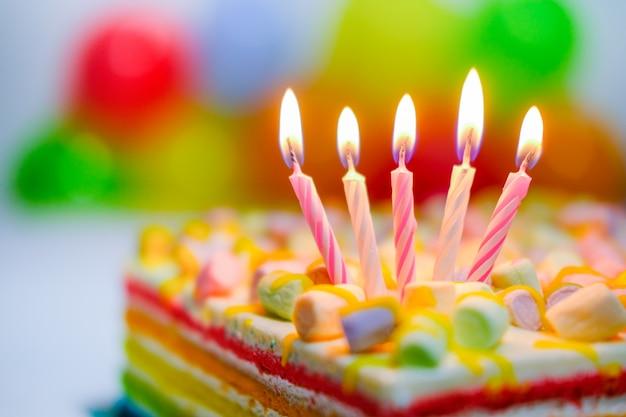 Tarjeta de cumpleaños colorida festiva con cinco velas encendidas en pastel de arco iris y globos de colores en el fondo. espacio para texto de felicitación.