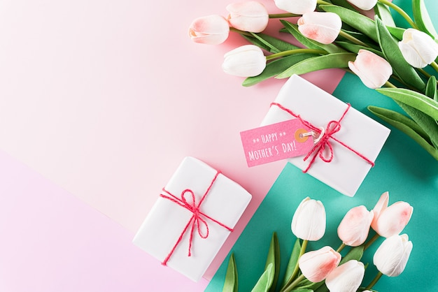 Tarjeta del día de la madre feliz, caja de regalo con tulipán en la pared de colores pastel
