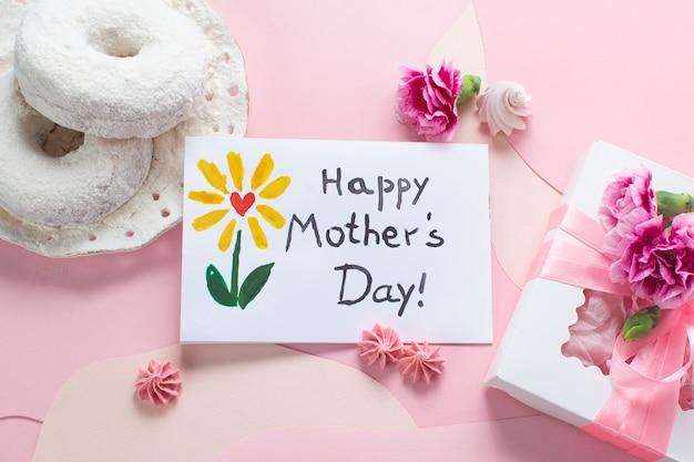 Tarjeta del día de la madre con flores rosas y doghnuts blancos sobre fondo rosa