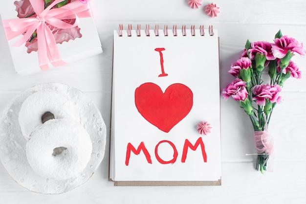 Tarjeta del día de la madre. texto amo a mamá. desayuno, donat, clavel, obsequio y postal hecha por el niño para mamá.