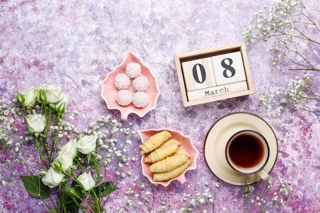 Tarjeta del día de la mujer del 8 de marzo con flores blancas, dulces y una taza de té
