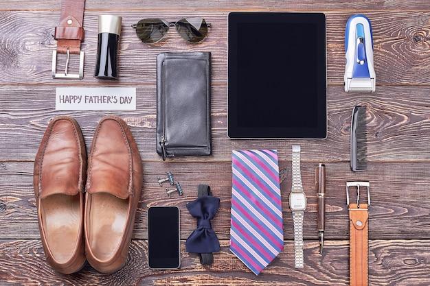 Tarjeta del día del padre cerca de accesorios. colonia, tableta y gafas de sol. tendencias de la moda masculina moderna.
