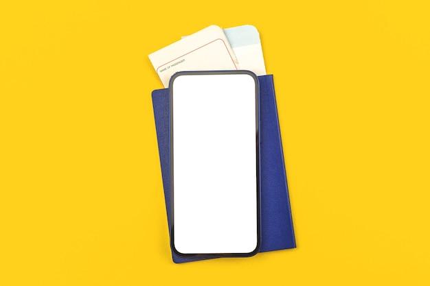 Tarjeta de embarque con pasaporte y maqueta de teléfono inteligente, pantalla blanca en blanco con espacio de copia, fondo de escritorio de oficina amarillo, prepararse para el concepto de viaje