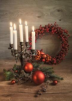 Tarjeta de felicitación con adornos navideños, corona y velas encendidas en madera