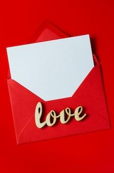 Tarjeta de felicitación con amor sobre rojo con papel blanco en blanco. maqueta de carta de amor.