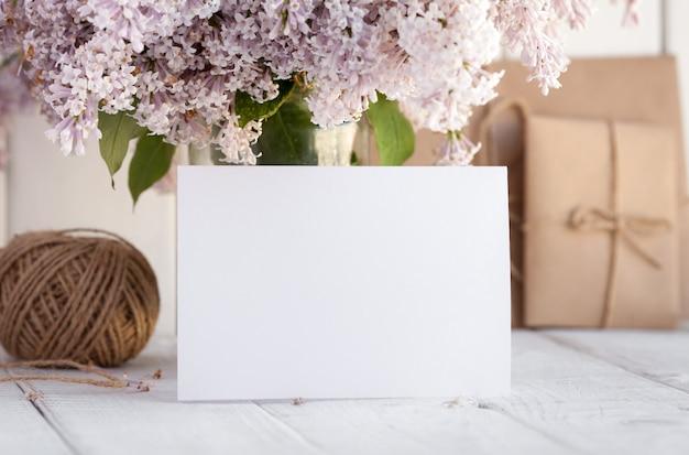 Tarjeta de felicitación blanca en blanco con flores lilas.