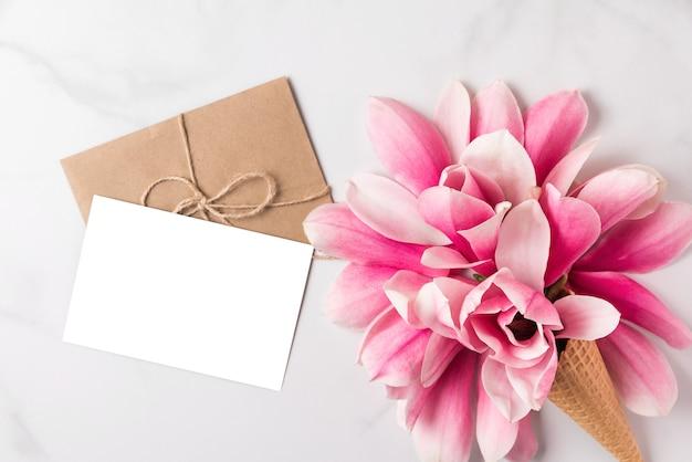 Tarjeta de felicitación blanca en blanco con flores de magnolia rosa primavera en cono de waffle.