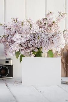 Tarjeta de felicitación blanca en blanco con ramo de flores lila.