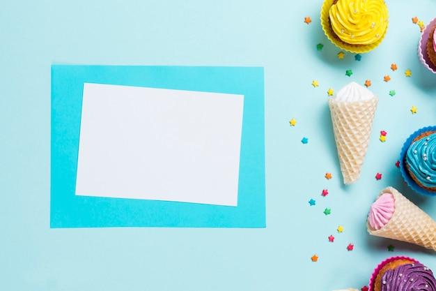 Tarjeta de felicitación en blanco cerca de los sprinkles; conos de gofres y muffins sobre fondo azul