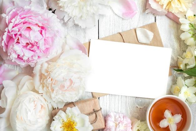 Tarjeta de felicitación en blanco en marco de flores de peonía, rosa y jazmín con taza de té