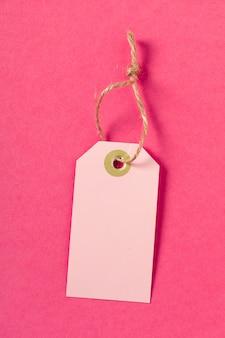 Tarjeta de felicitación en blanco o etiqueta en superficie rosa