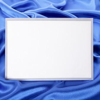 Tarjeta de felicitación en blanco o invitación con fondo de satén azul.