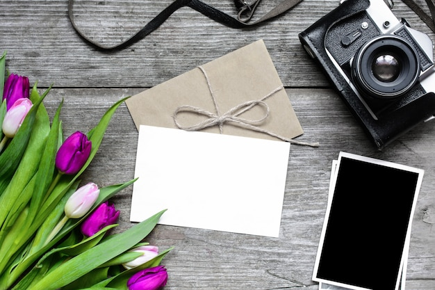 Tarjeta de felicitación en blanco y sobre con cámara retro, fotos en blanco