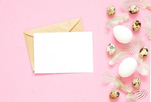 Tarjeta de felicitación en blanco, sobre kraft. composición de pascua con los huevos y las plumas de pascua en fondo rosado.