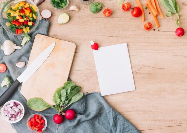 Tarjeta de felicitación en blanco con verduras frescas para ensalada en mesa de madera