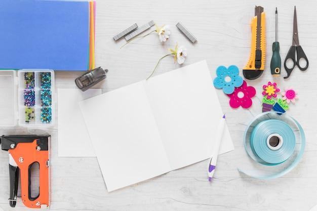 Tarjeta de felicitación de bloc de notas en blanco con elementos de pluma y artesanía