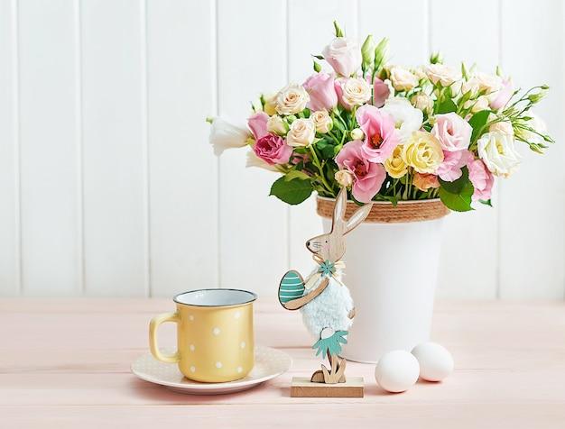 Tarjeta de felicitación de conejito floral de pascua feliz. mesa de pascua con huevos, conejo y flores.
