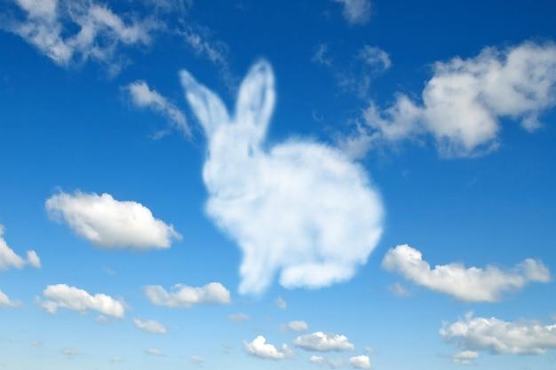 Tarjeta de felicitación de conejito de pascua esponjoso de nube blanca sobre un fondo azul cielo nublado con espacio de copia. enhorabuena tarjeta de pascua feliz.