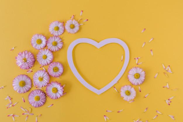 Tarjeta de felicitación con corazón y margaritas sobre un fondo naranja