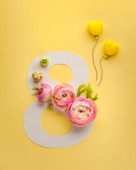 Tarjeta de felicitación del día internacional de la mujer el 8 de marzo. el ranúnculo rosa adorna el número ocho sobre fondo amarillo.