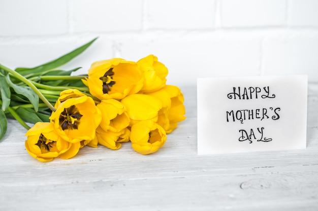Tarjeta de felicitación para el día de la madre y tulipanes amarillos en mesa de madera