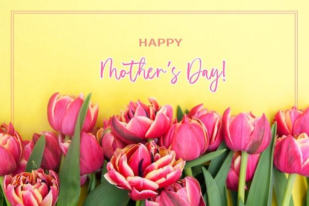 Tarjeta de felicitación del día de la madre con tulipanes rosa vista superior sobre un fondo amarillo