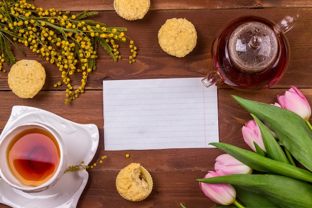 Tarjeta de felicitación del día de las mujeres con los tulipanes, la mimosa, el té y las magdalenas en fondo de madera marrón.