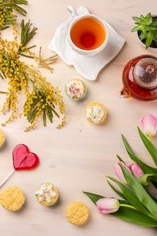 Tarjeta de felicitación del día de las mujeres con los tulipanes, la mimosa, el té y las magdalenas en fondo de madera.