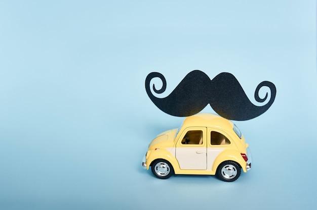 Tarjeta de felicitación del día del padre con carro de juguete amarillo y bigote de papel negro