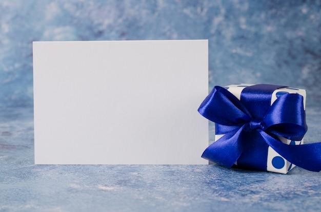 Tarjeta de felicitación para el día del padre o cumpleaños. caja de regalo con papel blanco en blanco sobre fondo azul.