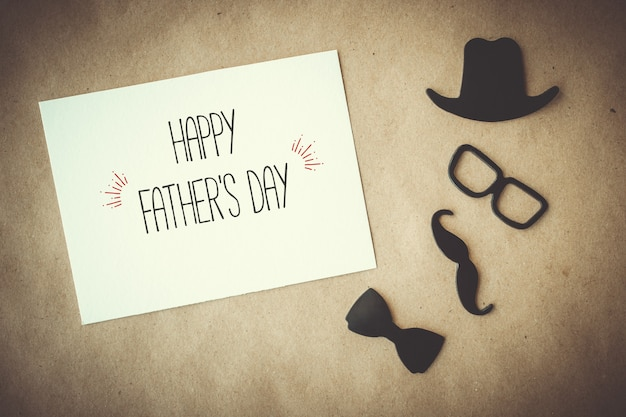 Tarjeta de felicitación del día del padre. tarjeta blanca con elementos decorativos sobre fondo de papel artesanal.