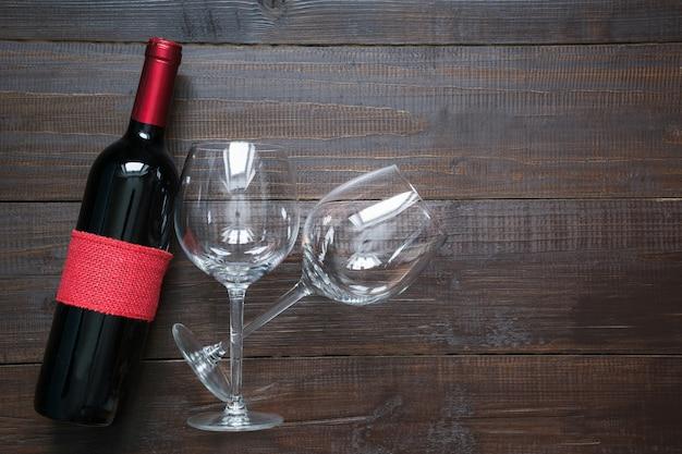 Tarjeta de felicitación del día de san valentín con botella de vino y vasos sobre tabla de madera. vista superior con espacio.