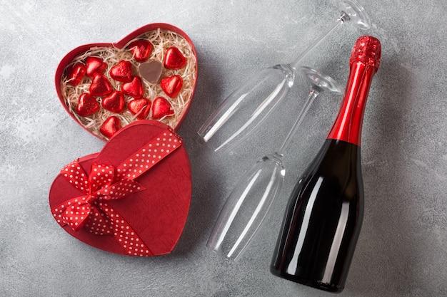 Tarjeta de felicitación del día de san valentín con copas de champán y corazones de caramelo sobre fondo de piedra.
