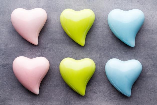 Tarjeta de felicitación del día de san valentín. corazón de color sobre fondo gris. vista desde arriba. endecha plana.