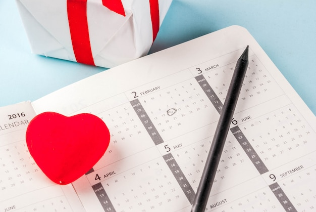 Tarjeta de felicitación del día de san valentín. corazón rojo con caja de regalo sobre el calendario de febrero sobre fondo azul claro. copiar espacio para saludos