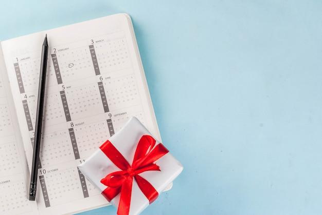 Tarjeta de felicitación del día de san valentín. corazón rojo con caja de regalo sobre calendario de febrero