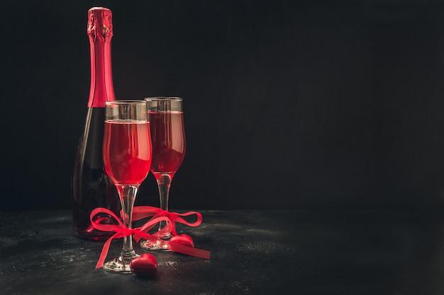Tarjeta de felicitación del día de san valentín y cumpleaños con champagne y dulces de corazón en negro.