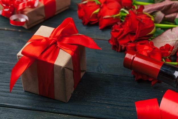 Tarjeta de felicitación del día de san valentín. flores rosas rojas, vino y caja de regalo en mesa de madera.