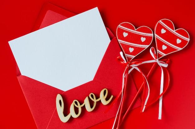 Tarjeta de felicitación para el día de san valentín. sobre rojo con papel blanco en blanco. maqueta de carta de amor.