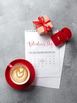 Tarjeta de felicitación del día de san valentín. taza de café roja, anillo y caja de regalo en el calendario de febrero. vista desde arriba