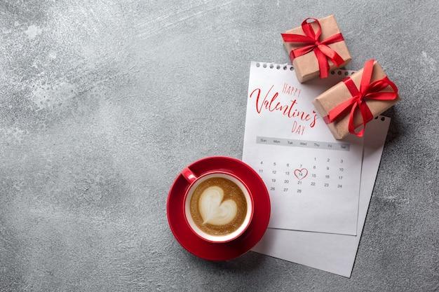 Tarjeta de felicitación del día de san valentín. taza de café roja y caja de regalo en el calendario de febrero. vista superior