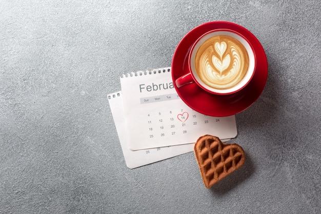 Tarjeta de felicitación del día de tarjeta del día de san valentín con la taza de café y las galletas en forma de corazón en fondo gris.