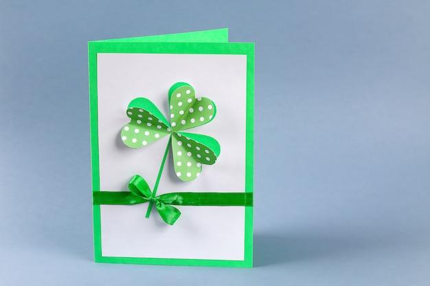 La tarjeta de felicitación diy st patricks day hizo cartón y tréboles de papel fondo gris
