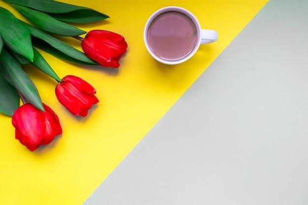 Tarjeta de felicitación de endecha plana tulipanes rojos frescos y una taza de café para su texto