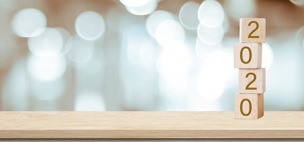Tarjeta de felicitación de feliz año nuevo 2020, cubos de madera con 2020 sobre desenfoque de fondo bokeh con espacio de copia