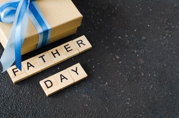 Tarjeta de felicitación feliz del día de padre con la caja de regalo adornada en fondo oscuro.