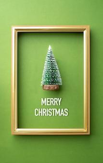 Tarjeta de felicitación de feliz navidad, árbol de navidad verde con marco dorado en verde